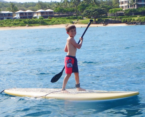 Boy learning to paddle board on Maui